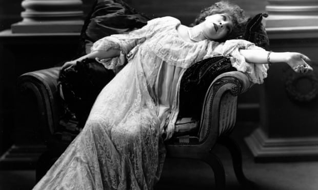 A black and white photograph of Sarah Bernhardt reclining dramatically in an armchair.